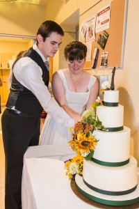 """Cutting the """"local food"""" wedding cake! (Decorated with flowers from Seeley Farm!)"""